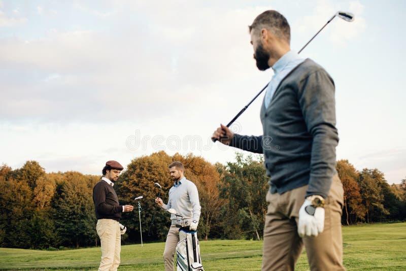 Golfistas multiétnicos felices que pasan el tiempo junto en campo de golf fotos de archivo libres de regalías