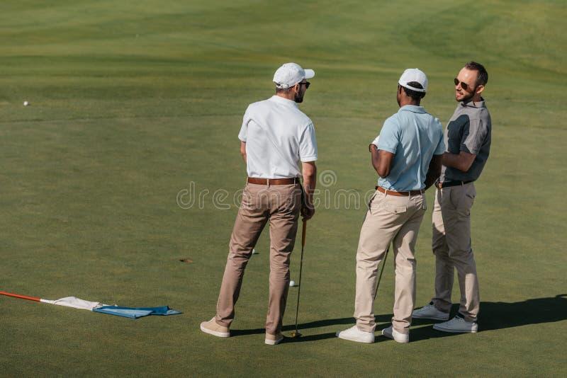Golfistas profesionales que hablan mientras que se coloca en echada verde fotos de archivo
