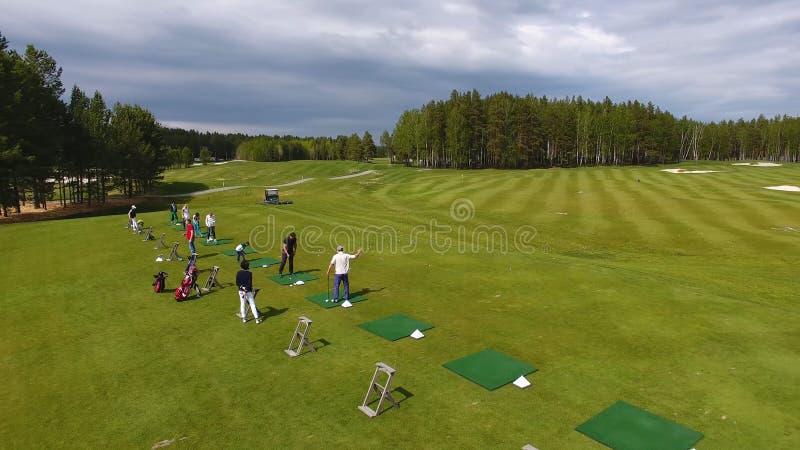 Golfistas que golpean el tiro de golf con el club en curso mientras que el las vacaciones de verano, aéreas fotos de archivo libres de regalías