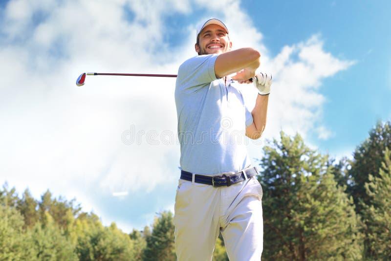 Golfisty ciupni?cia golfa strza? z klubem na kursie podczas gdy na wakacje zdjęcie royalty free