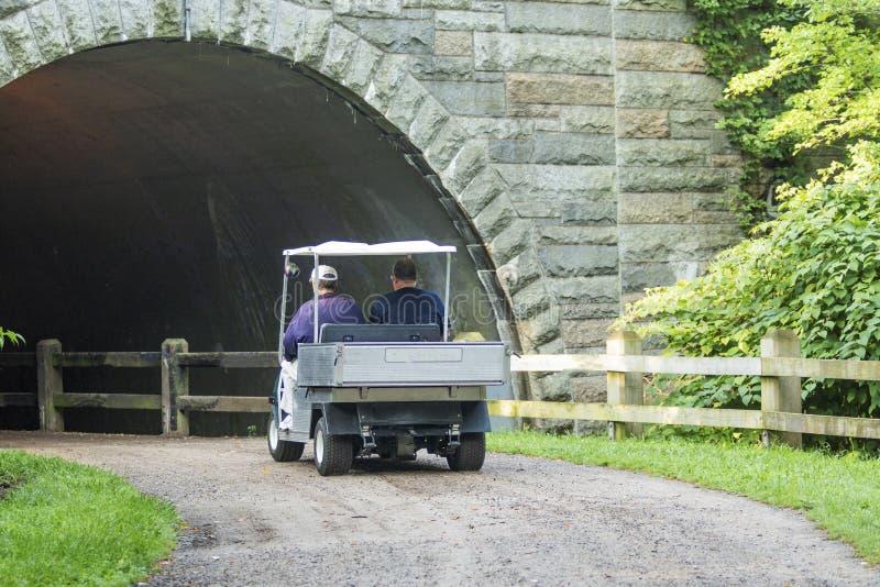 Golfkar op vuilweg die onder een brug gaan royalty-vrije stock afbeeldingen