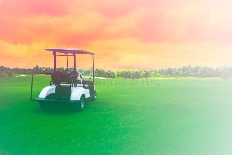 Golfkarretauto in een vaarbaan voor een golfbaan met vers groen grasveld en wolkenachtergrond royalty-vrije stock afbeeldingen