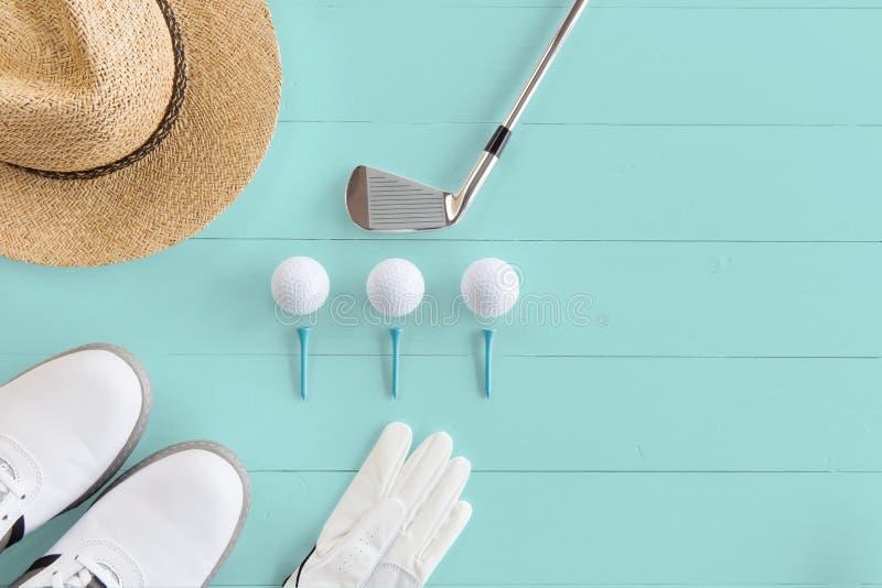 Golfklubb, golfbollar, golfskor och utslagsplatser på en träyttersida i turkos, bästa sikt, kopieringsutrymme royaltyfri bild