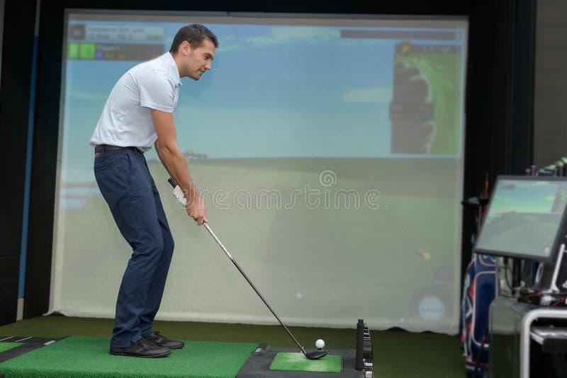 Golfowy gracz bawić się gra wideo golfa indoors obrazy stock