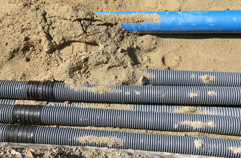 Golfpijpen voor het leggen van elektrische kabels in de uitgraving royalty-vrije stock afbeeldingen