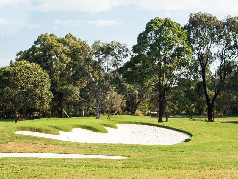 Golfplatz mit grünem Gras und kleiner Sandgrube lizenzfreie stockfotografie