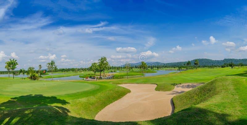 Golfplatzgrün unter blauem Wolkenhimmel für Szenenhintergrund stockfotos