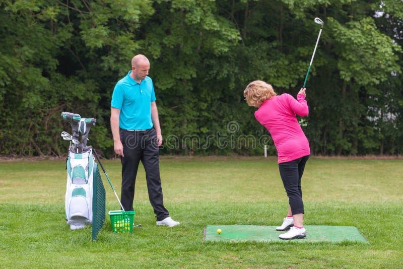 Golfpro, einen Damengolfspielerdurchschwung festsetzend stockfotos