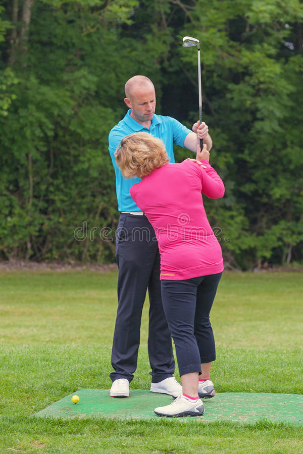 Golfpro, einen Damengolfspielergriff korrigierend lizenzfreie stockfotografie