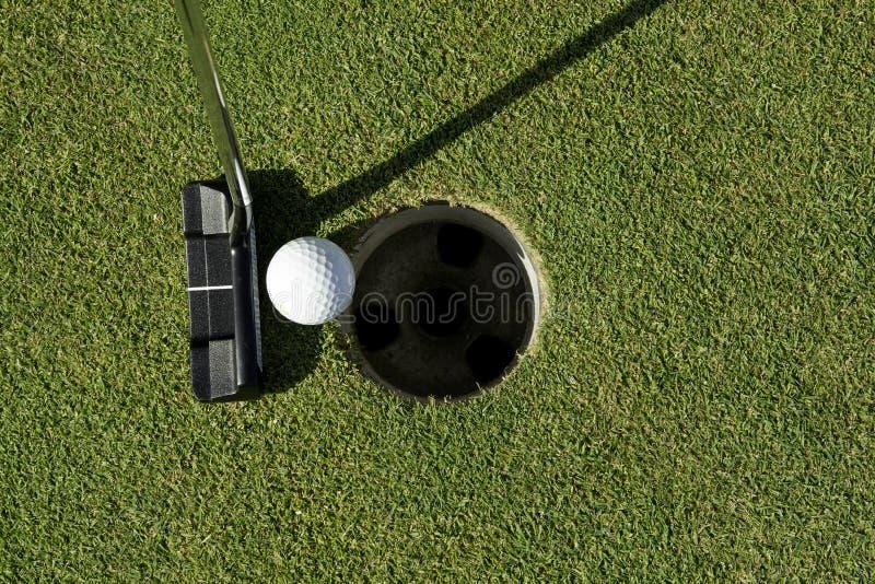 Golfputter och boll bredvid koppen royaltyfria bilder