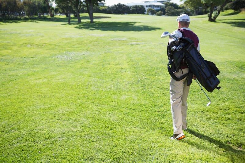 Golfspelare som bär hans påse och gå royaltyfri foto