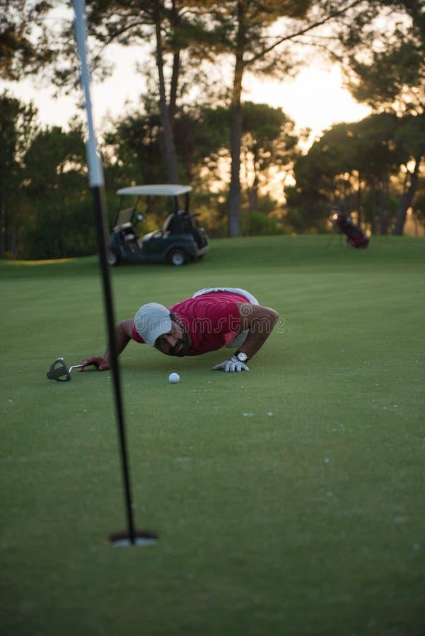 Golfspelare som blåser bollen i hål med solnedgång i bakgrund royaltyfri foto