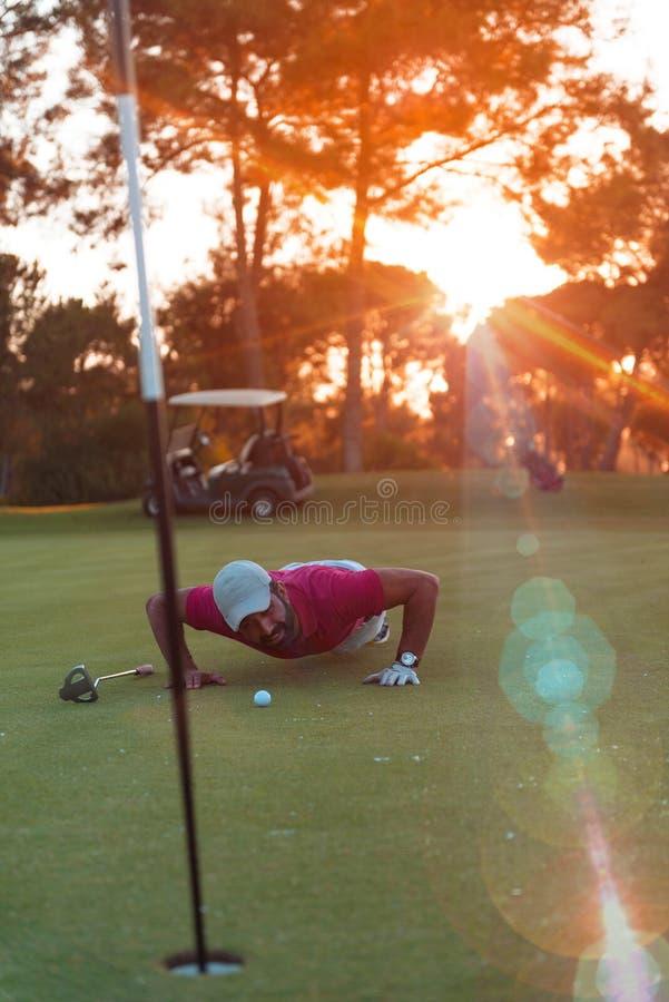 Golfspelare som blåser bollen i hål med solnedgång i bakgrund arkivbild