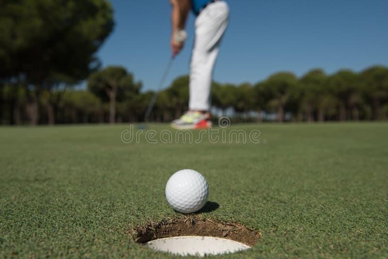 Golfspelare som slår skottet, boll på kanten av hålet fotografering för bildbyråer