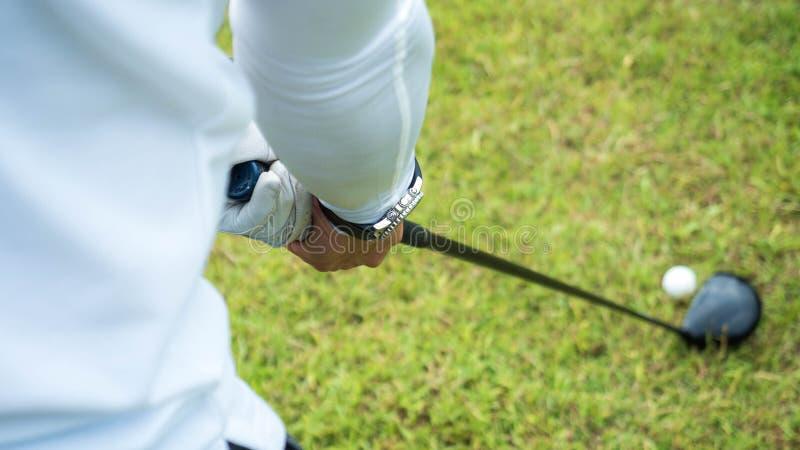 Golfspelaren som slår det härliga skottet med klubban på kurs i, parkerar arkivbilder