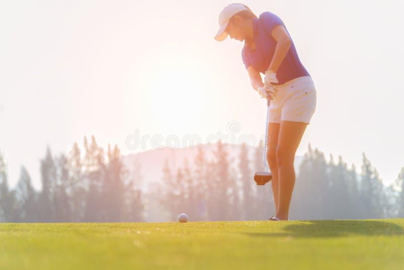 Golfspeler Aziatische vrouw die golfbal op het groene golf op tijd van de zon de vastgestelde avond zetten stock foto's