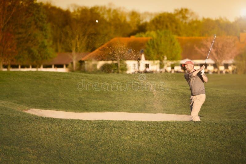 Golfspeler bij bunker stock afbeeldingen