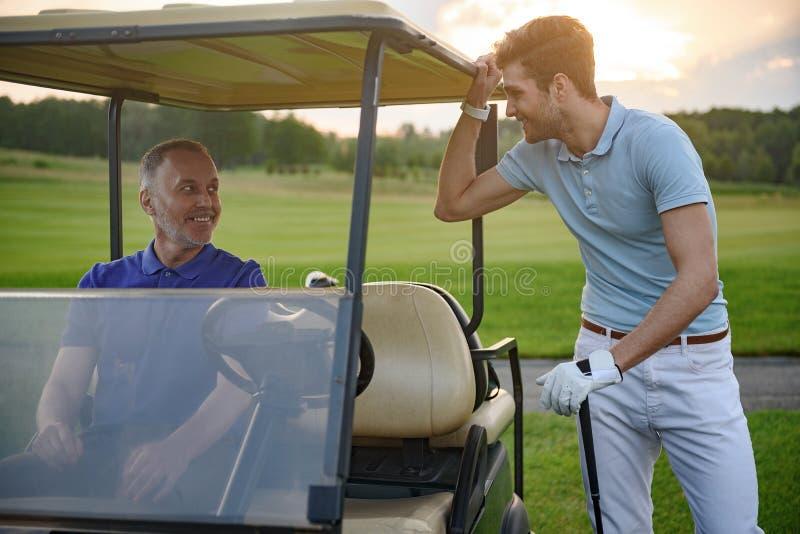 Golfspeler dichtbij golfkar royalty-vrije stock afbeelding