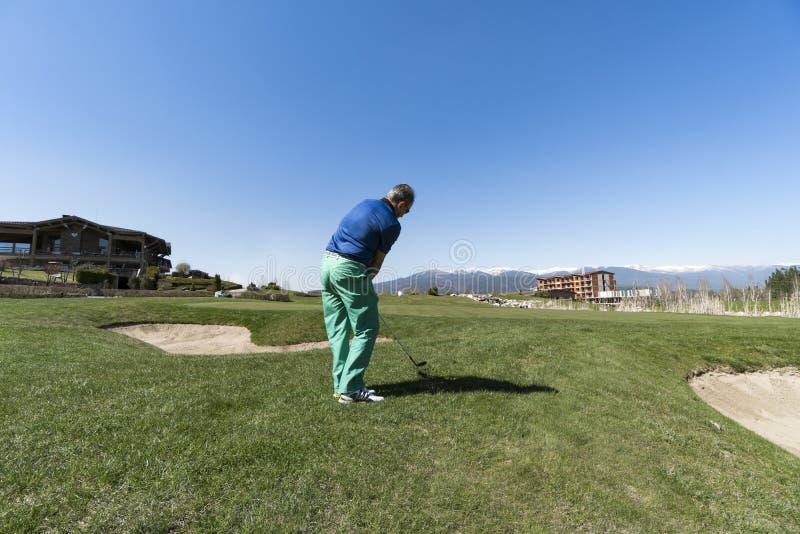 Golfspeler die Bal met Club raken stock afbeelding