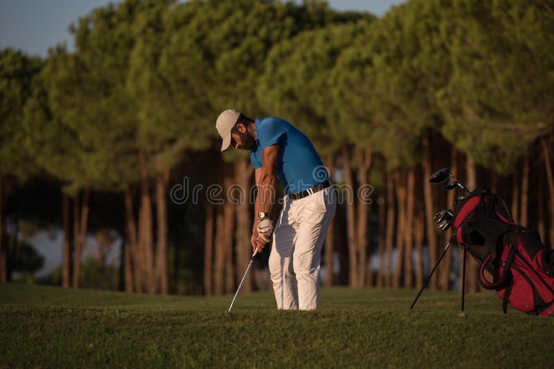 Golfspeler die die een zandbunker raken op zonsondergang wordt geschoten stock foto