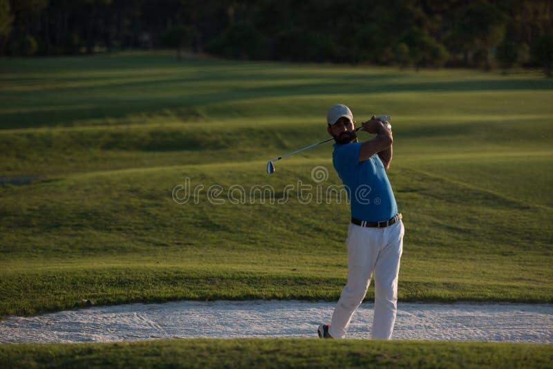 Golfspeler die die een zandbunker raken op zonsondergang wordt geschoten stock afbeelding