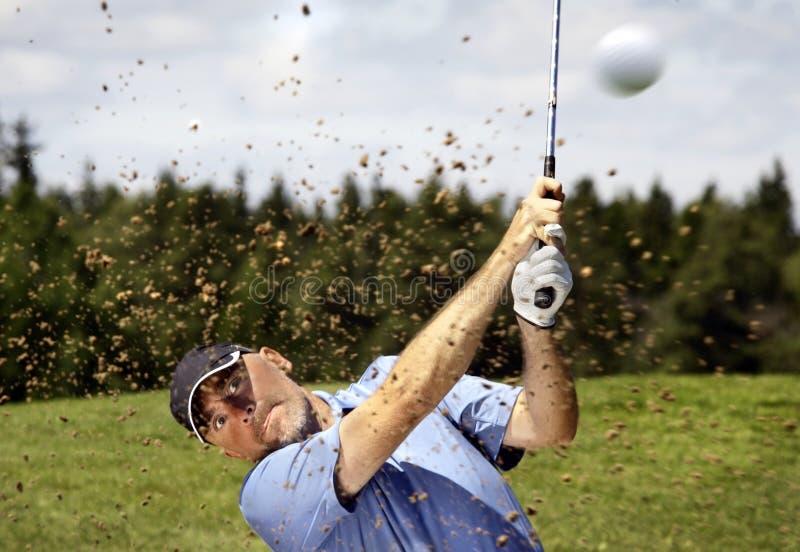 Golfspeler die een golfbal ontspruit stock foto