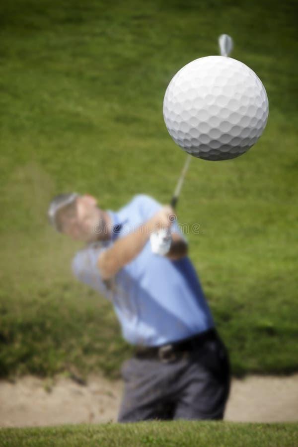 Golfspeler die een golfbal schiet stock afbeeldingen