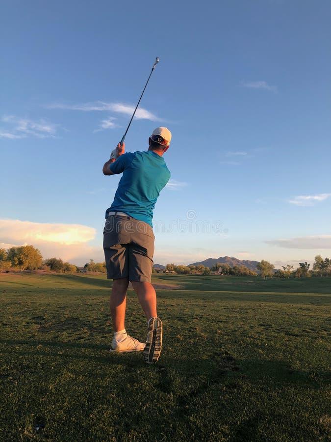Golfspeler die een golfbal van een achtermening raakt stock foto's