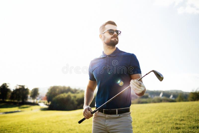 Golfspeler die een golfclub in golfcursus houden royalty-vrije stock foto