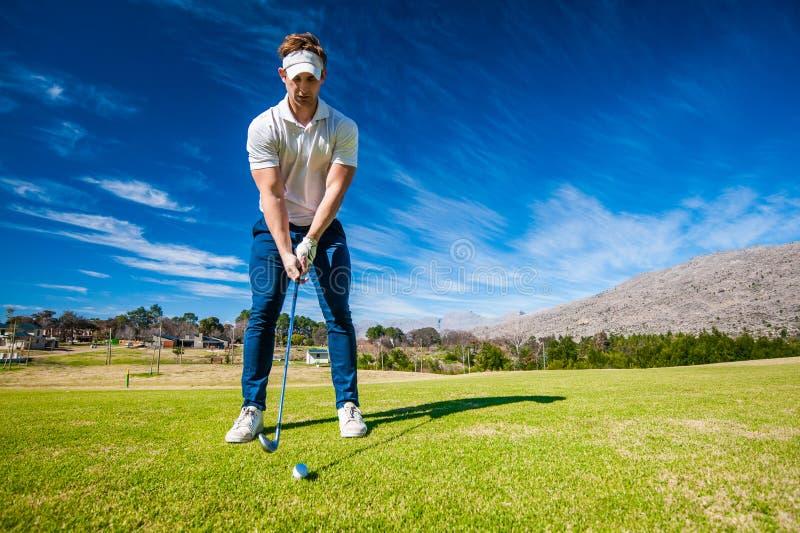 Golfspeler die een schot op fairway spelen stock afbeelding