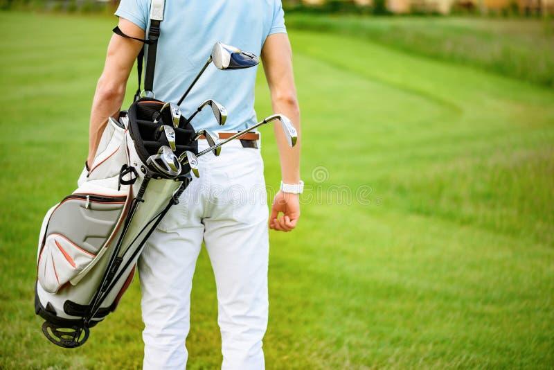 Golfspeler die met golfzakken lopen stock afbeeldingen