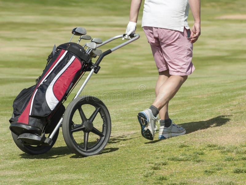 Golfspeler die op cursus met zak lopen stock fotografie