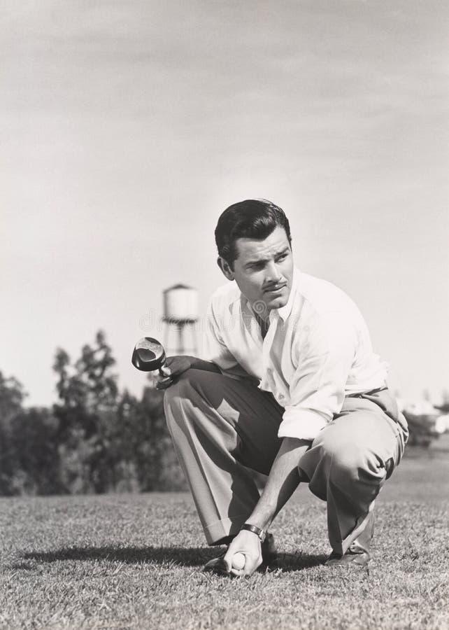 Golfspeler die op golfcursus buigen royalty-vrije stock foto