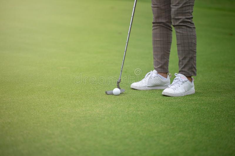 Golfspeler die op groen en Golfbal dichtbij Gat zetten stock foto's