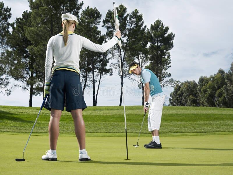 Golfspeler die op Groen zetten royalty-vrije stock fotografie