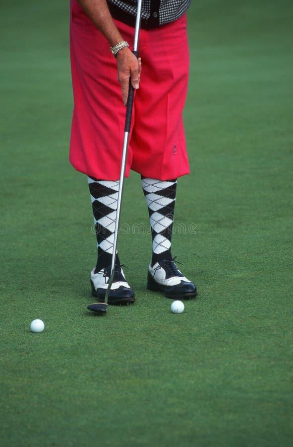 Golfspeler die roze golfbroek draagt stock afbeelding