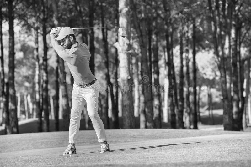 Golfspeler die schot met club raken stock foto