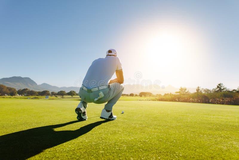 Golfspeler die schot op cursus streven royalty-vrije stock afbeeldingen