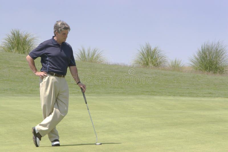 Golfspeler die tegen putter leunt stock afbeeldingen