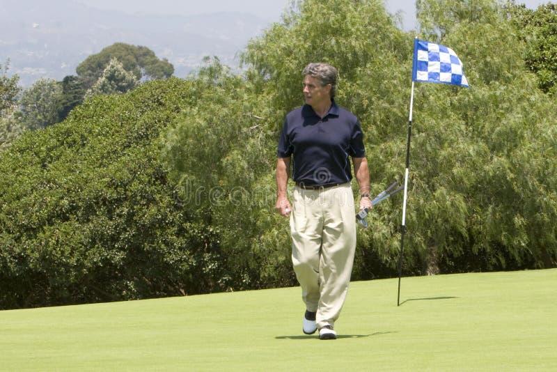 Golfspeler die van groen loopt royalty-vrije stock afbeeldingen