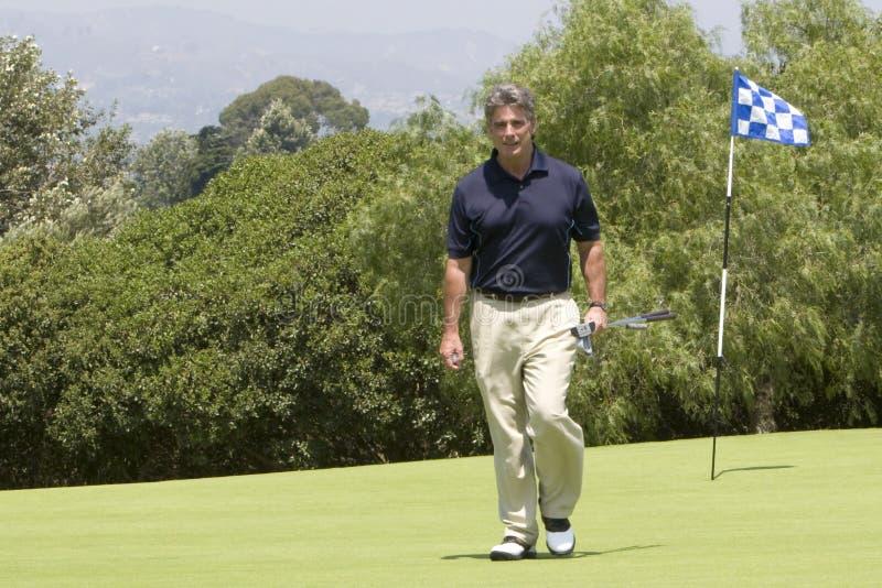 Golfspeler die van groen loopt   royalty-vrije stock afbeelding