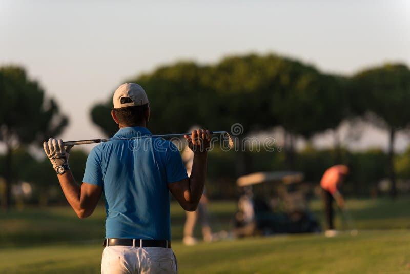 Golfspeler die van terug bij cursus aan gat in afstand kijken stock afbeeldingen