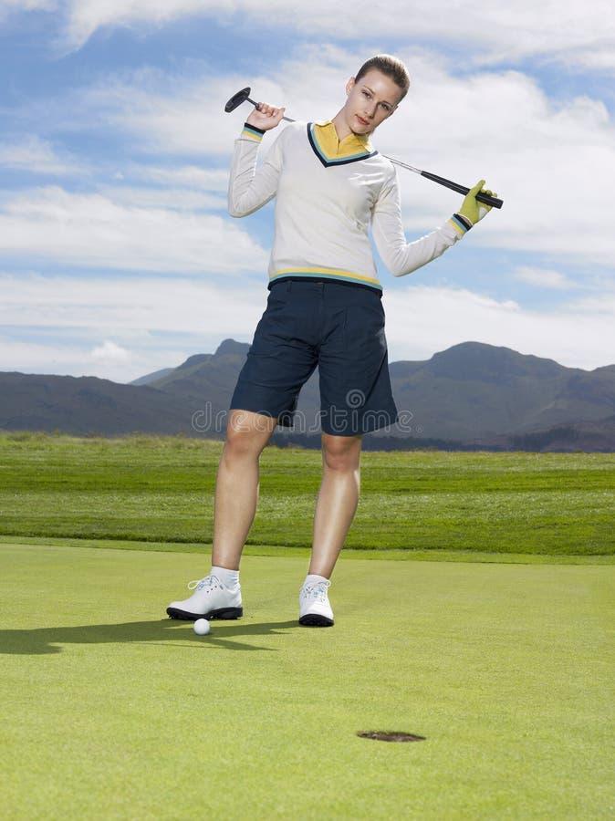 Golfspeler met Club die zich op Groen bevinden royalty-vrije stock foto