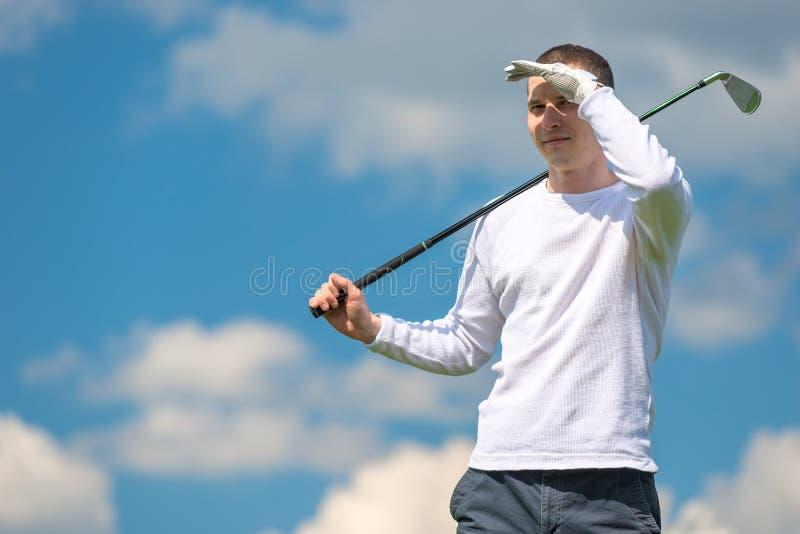 Golfspeler met een golfclub op een zonnige dag stock afbeeldingen