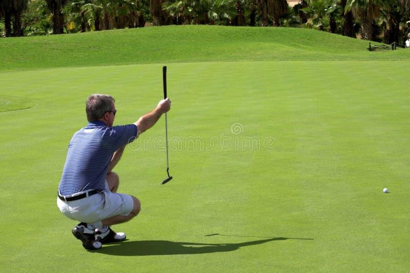 Golfspeler op green stock foto