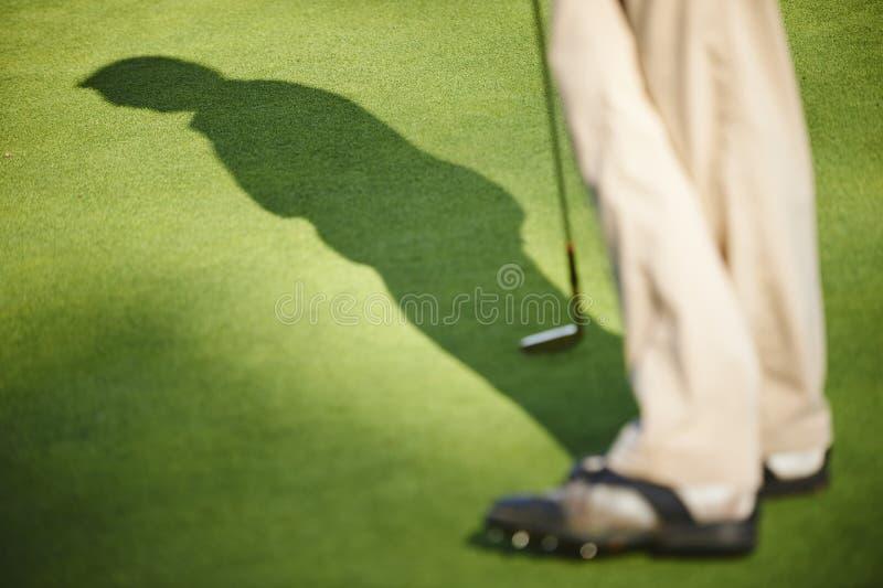 Golfspeler op green wordt bevonden die stock afbeelding