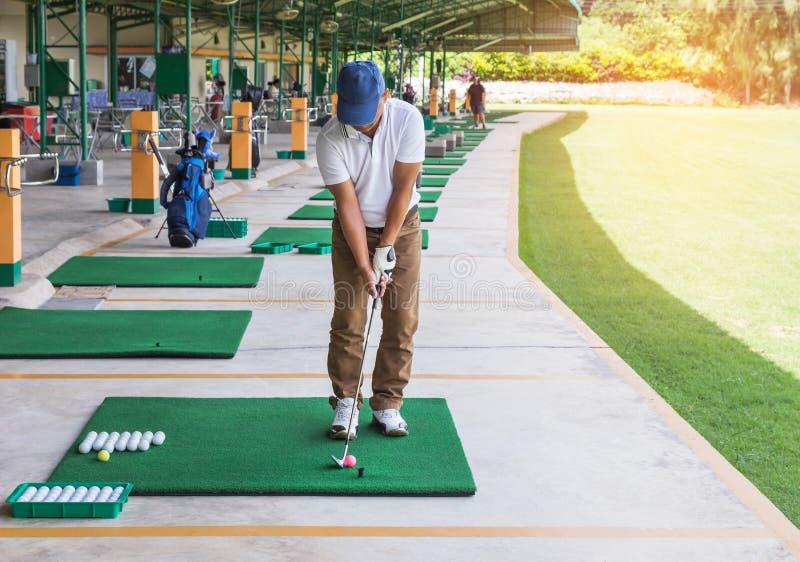 Golfspeler tijdens praktijk drijfwaaier in golfcursus stock foto