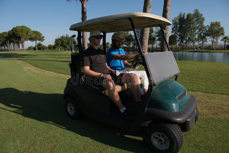 Golfspelers die kar drijven bij cursus stock afbeeldingen