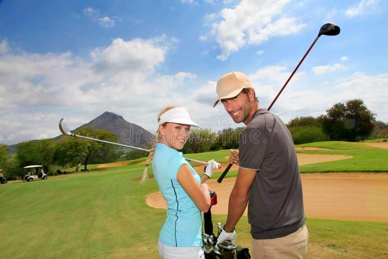 Golfspelers op golfcursus stock foto's