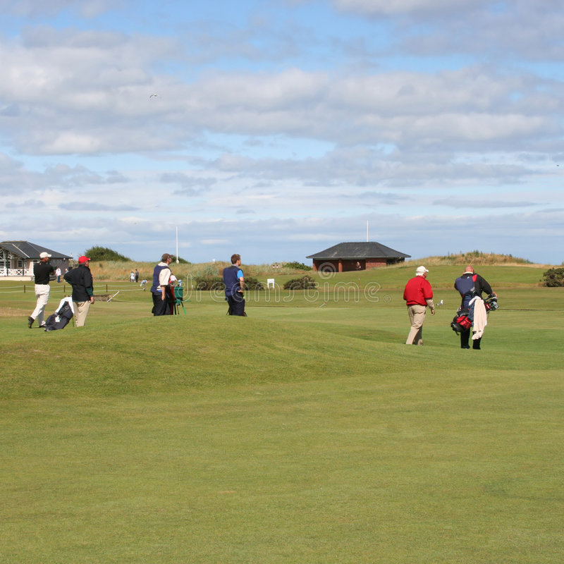 Golfspelers op golfcursus stock afbeeldingen